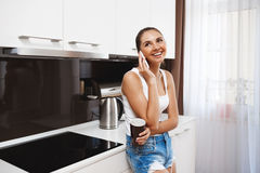 Beautiful smiling young girl  talking on phone at kitchen and drinking a coffee Stock Photos