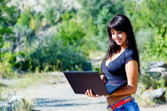 Beautiful smiling young hispanic woman working on laptop outdoor Royalty Free Stock Photo