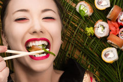 Beautiful smiling young Korean girl eating sushi rolls Royalty Free Stock Photos