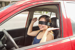 Beautiful smiling young lady with a black rag covered her eyes, while the car drives by itself Stock Photography