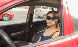 Beautiful smiling young lady with a black rag covered her eyes, while the car drives by itself Royalty Free Stock Images