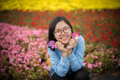Beautiful smiling young lady holding petals squats at flower garden. Royalty Free Stock Photos