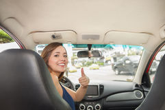 Beautiful smiling young lady with thumbs up watching back seats, while the car drives by itself Royalty Free Stock Photos