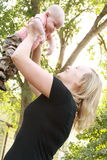 Beautiful, smiling young mother holds her baby boy up in outstretched arms. Royalty Free Stock Photography