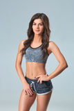 Beautiful smiling young sportswoman in gray top and black shorts standing on gray background Royalty Free Stock Photos