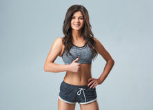 Beautiful smiling young sportswoman in gray top and black shorts standing on gray background Stock Images