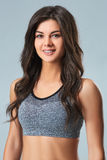 Beautiful smiling young sportswoman in gray top and black shorts standing on gray background Royalty Free Stock Image