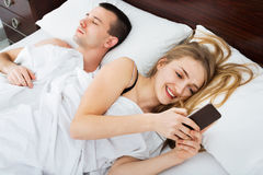 Beautiful smiling young  wife texting with lover on smartphone Stock Photo