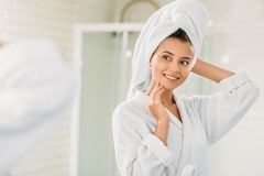 Beautiful smiling young woman in bathrobe and towel on head looking at mirror. In bathroom stock photo