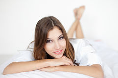 Beautiful smiling young woman on bed Stock Photos