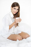 Beautiful smiling young woman on bed with cup of coffee Royalty Free Stock Photo