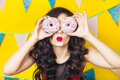 Beautiful smiling young  woman with a donut. Celebration and party. Beauty girl taking colorful donuts. Funny joyful woman with sweets, dessert. Diet, dieting Stock Images