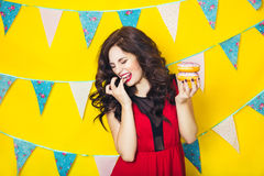 Beautiful smiling young  woman with a donut. Celebration and party. Beauty girl taking colorful donuts. Funny joyful woman with sweets, dessert. Diet, dieting Royalty Free Stock Image