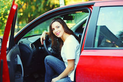 Beautiful smiling young woman driver behind wheel red car Stock Photos
