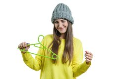 Beautiful smiling young woman with empty clothes hanger, autumn winter season, girl in sweater and knitted hat, isolated on white royalty free stock photography