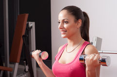 Beautiful smiling young woman exercising with dumbbells Stock Photo