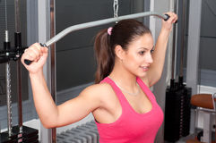 Beautiful smiling young woman exercising with weights. In the gym Royalty Free Stock Photography