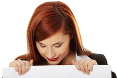 Beautiful smiling young woman holding a blank sign Stock Image