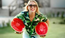 Beautiful smiling young woman holding sweet juicy watermelon in hands stock images