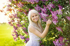 Beautiful smiling young woman with lilac flowers Royalty Free Stock Photography