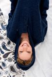 A smiling young woman lying on a bed in a blue sweatshirt Stock Photography