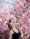 Beautiful smiling young woman near the blossoming spring tree. Portrait of pretty blond girl with long hair in pink flowers. Royalty Free Stock Images