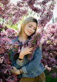 Beautiful smiling young woman near the blossoming spring tree. Portrait of pretty blond girl with long hair in pink flowers. Royalty Free Stock Photography