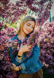 Beautiful smiling young woman near the blossoming spring tree. Portrait of pretty blond girl with long hair in pink flowers. Stock Photo