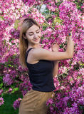 Beautiful smiling young woman near the blossoming spring tree. Portrait of pretty blond girl with long hair in pink flowers. Stock Photos
