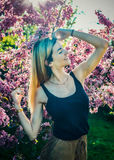 Beautiful smiling young woman near the blossoming spring tree. Portrait of pretty blond girl with long hair in pink flowers. Royalty Free Stock Photo