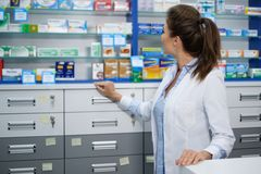 Beautiful smiling young woman pharmacist doing his work in pharmacy. stock images