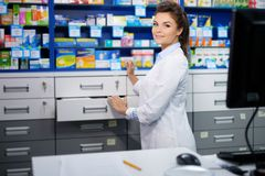 Beautiful smiling young woman pharmacist doing his work in pharmacy. stock photos