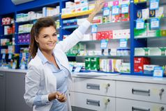 Beautiful smiling young woman pharmacist doing his work in pharmacy. stock image