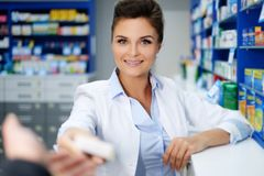 Beautiful smiling young woman pharmacist doing his work in pharmacy. stock photography