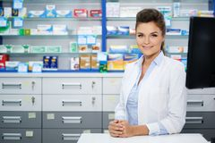 Beautiful smiling young woman pharmacist doing his work in pharmacy. royalty free stock photo