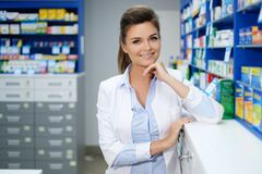 Beautiful smiling young woman pharmacist doing his work in pharmacy. stock photo