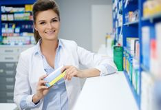 Beautiful smiling young woman pharmacist doing his work in pharmacy. royalty free stock images