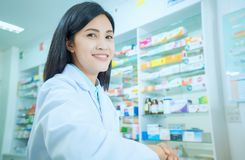 Beautiful smiling young woman pharmacist doing his work in pharmacy royalty free stock images