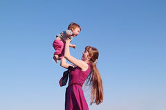 Beautiful smiling young woman in pink dress holding her son Stock Photos