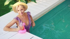 Beautiful smiling young woman relaxes in the pool on a sunny day stock footage