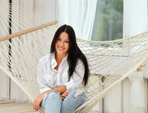 Beautiful smiling  young woman relaxing in hammock at home Royalty Free Stock Photography