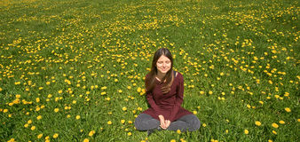 Beautiful smiling young woman relaxing on a meadow with many dandelions in the spring sun. Frontal view with copyspace. Beautiful young woman relaxing on a royalty free stock photo