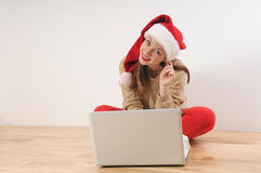 Beautiful smiling young woman in santa hat searching online pres Royalty Free Stock Images