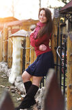 Beautiful smiling young woman in scarf red pullover posing alone against yard and sunset light. Beautiful smiling young woman in scarf red pullover posing alone Royalty Free Stock Images