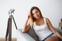 Beautiful smiling young woman sitting in the armchair in the living room looking at camera Royalty Free Stock Image