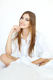 Beautiful smiling young woman sitting on bed Royalty Free Stock Photos