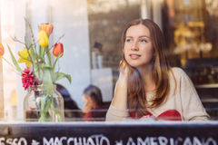 Beautiful smiling young woman sitting in cafe and thoughtfully looking out of the window.  Stock Photography