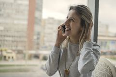 Beautiful smiling young woman sitting indoors and talking on mob. Ile phone. Girls time, enjoying, lifestyle Stock Photography