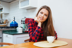Beautiful smiling young woman sitting on kithen and drinking coffee Royalty Free Stock Photos