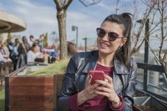 Beautiful smiling young woman sitting outdoors and chatting on m. Obile phone. Girls time, enjoying, lifestyle Stock Photos